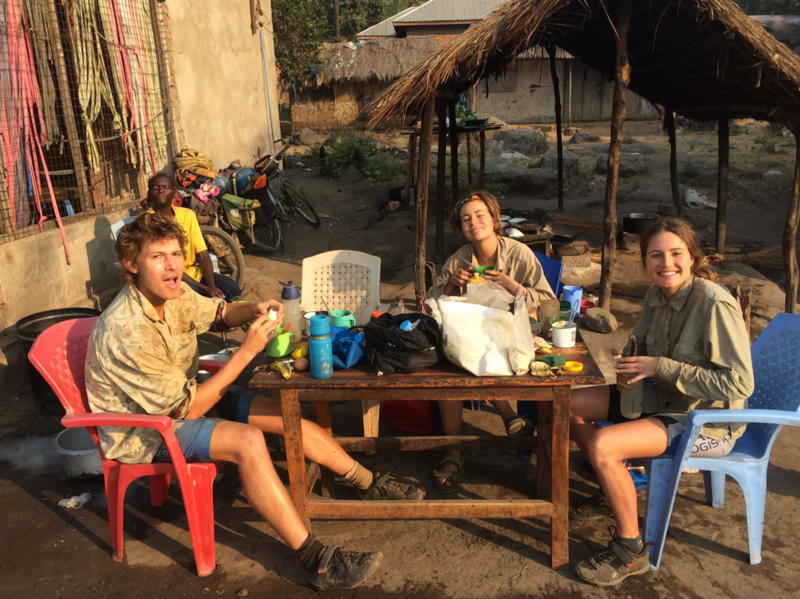 Three of the riders eating whilst sat at an outdoor table which is covered with their bags, flasks and mugs