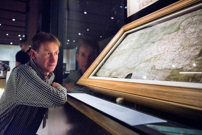 Nick Millea looking at a map which is mounted within a glass  case in a museum