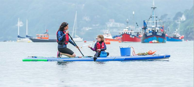 A mother and daughter sat on a paddleboard at sea, with buckets and litter on the paddleboard, and boats in the background