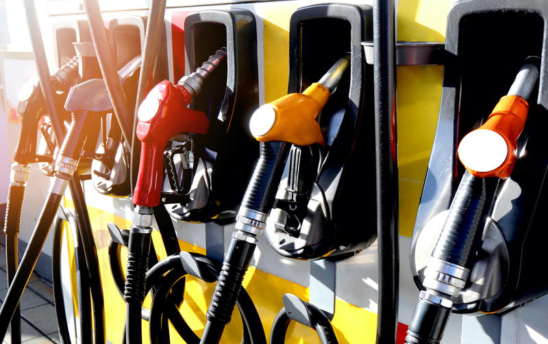 Petrol station filling nozzles, brightly coloured amidst sunshine