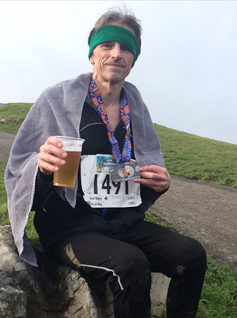 Phil, wearing running kit and a race number, holding a beer and displaying his medal for the camera, whilst sat on a large stone with the sea in the distance