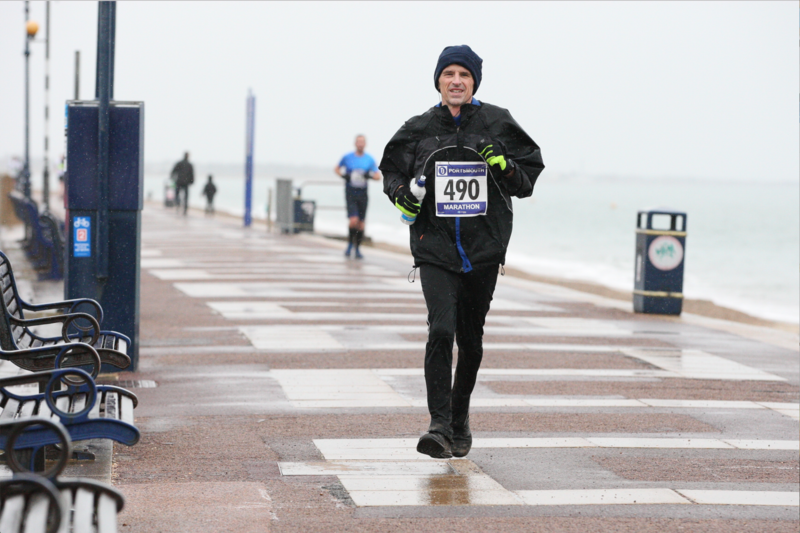 Phil Hewitt, dressed for winter weather and wearing a race number, running along a wet seafront