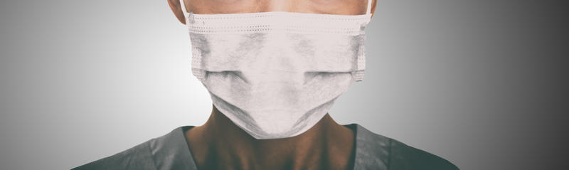 Someone in scrobs, wearing a surgical mask