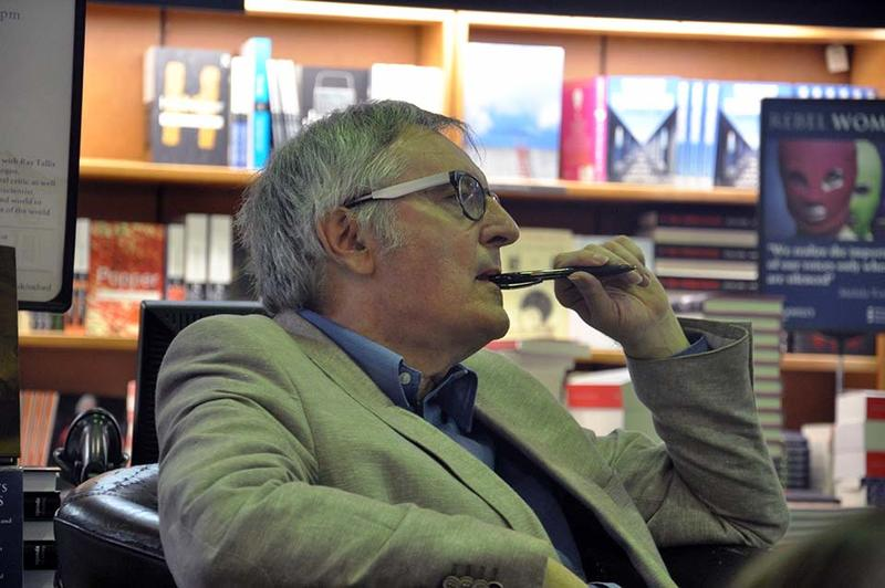 Professor John Gray, seated, listening to someone with a pen to his mouth