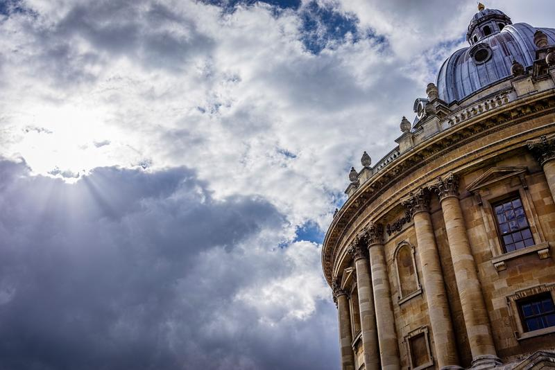 A view from groundlevel to the roof of the Radcliffe Camera, with a dark, cloudy sky behind it