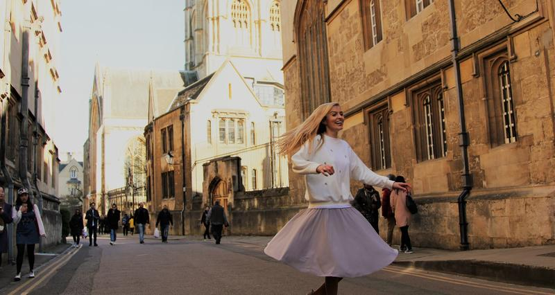 Tilly Rose spinning in a floaty skirt in the street outside Corpus Christi College