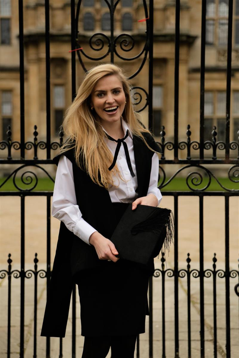 Tilly Rose, wearing sub fusc, outside the Examination Schools in Oxford