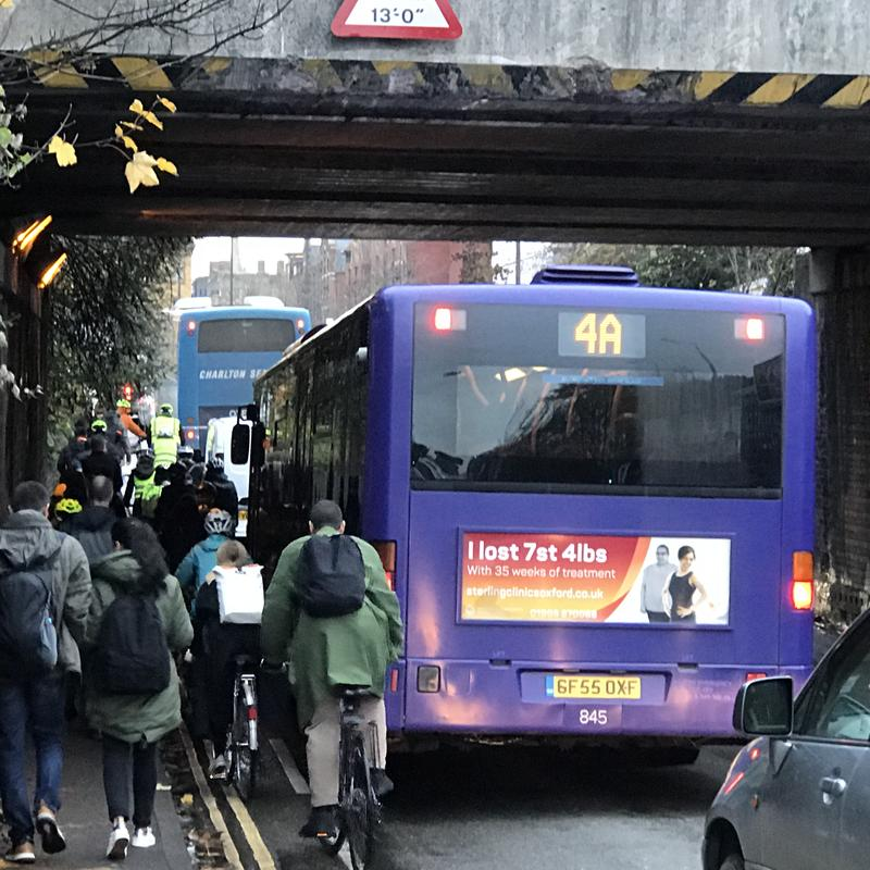 Traffic congestion on Botley Road, beneath the railway bridge, with cyclists' progress stopped by a bus