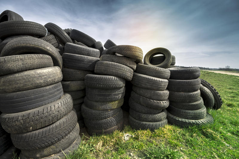 A pile of car tyres in a field