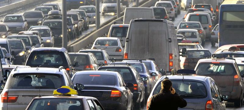 A traffic jam on both carraigeways of a motorway, with the air, and some cars, looking dirty