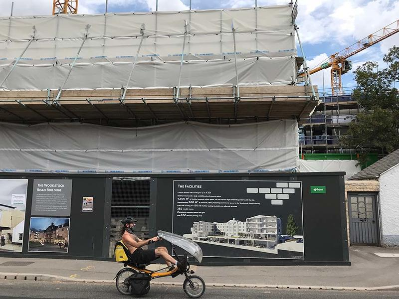 A construction site behind boards on which is a sign saying 'The Woodstock Road Building', with scaffolding covered in tarpaulins