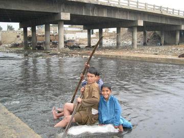 Still from Concrete Dreams children on a raft in Karachi