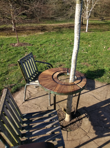 A picture of Havel's Place - a table surrounding a tree, with two chair, on a paved area