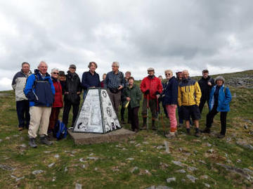 A group photo of 17 walkers stood next to a trig point on Bakestonedale Moor