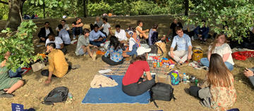 Students sat under trees having a picnic